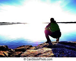 Man sit at evening sea. Hiker with backpack sit in squatting position  along beach.