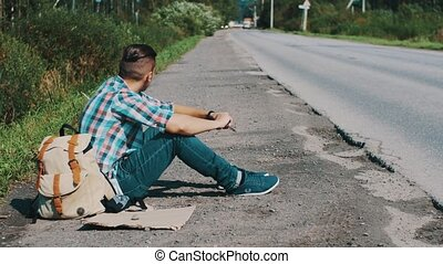 Man sit at road in countryside. Hitchhiking. Waiting for help. Grass in mouth.