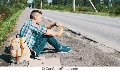 Man sit at road in countryside. Hitchhiking. Waiting for help. Eating banana.