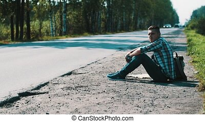 Man sit at road in countryside. Hitchhiking. Waiting for help. Smoking cigarette