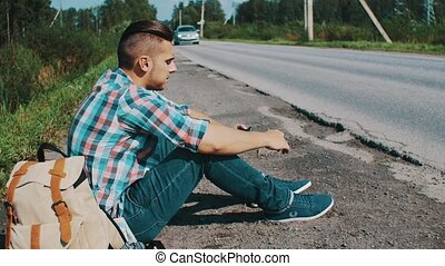 Man sit at road in countryside. Hitchhiking. Waiting. Pick up phone. Backpack