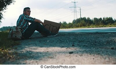 Man sit at road in countryside with cardboard plate sign...