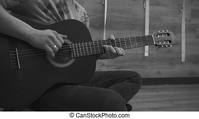 Man sits and plays acoustic guitar. Closeup. Black and White...