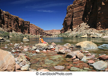 man sits by river