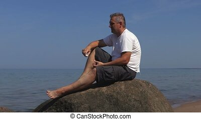 Man sits down the sea on a rock and relaxes