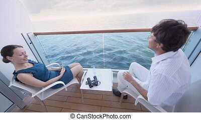 man sits near woman in fenced part of deck of ship and drinks water from glass