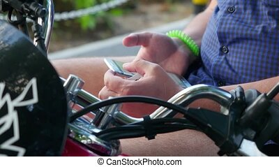 Man sits on retro motorbike uses phone in park, hipster concept. Close up of hands. 3840x2160