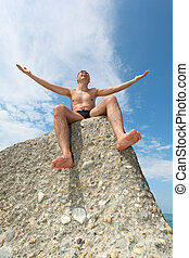 man sits on rock, bottom view