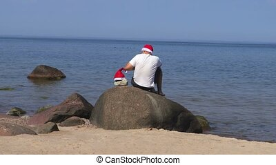 Man sits on rock on the seafront with Santa Claus hat