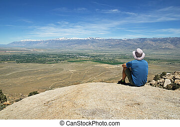 Man Sits On Rock Overlook