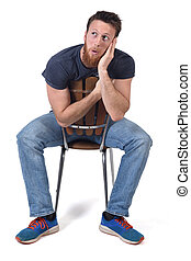 man sittin on a chair with expression of forgetfulness or surprise on white background