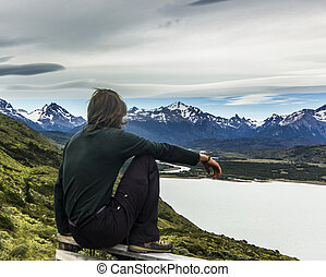 man sitting above lake in patagonia with grey sky