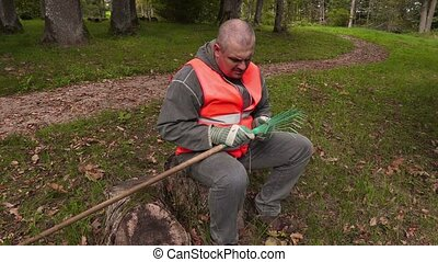 Man sitting and fix rake in park