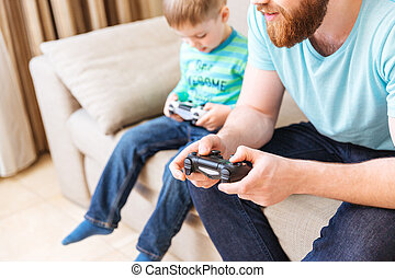 Man sitting and playing computer games with his little son