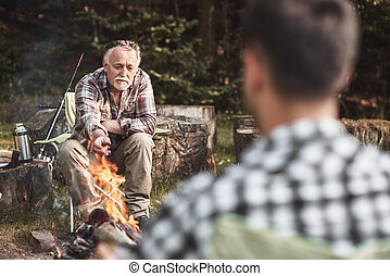 Man sitting around a campfire while camping in the forest