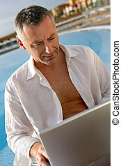 Man sitting at a poolside in front of a laptop computer