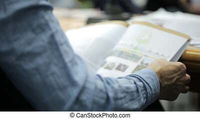 Man sitting at conference leafing through a magazine with charts and drawings.