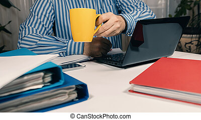 Man sitting at desk working with laptop from home