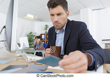 man sitting at his desk and looking at a laptop