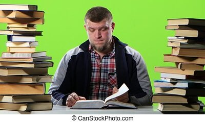 Man sitting at his desk leafing through a textbook. Green screen