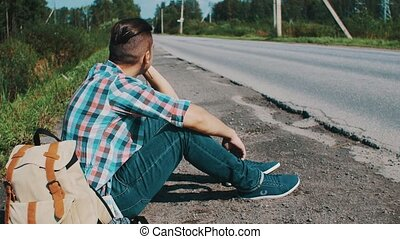 Man sitting at road in countryside. Hitchhiking. Waiting help. Speaking on phone