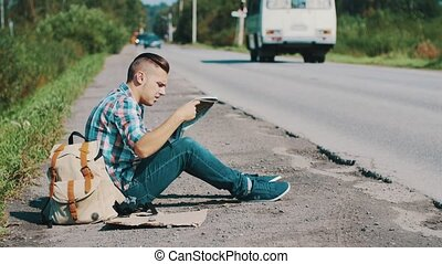 Man sitting at road in countryside. Hitchhiking. Waiting for help. Looking map.