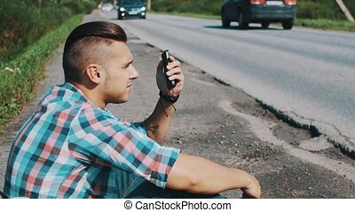 Man sitting at road in countryside. Hitchhiking. Waiting for help. Pick up phone