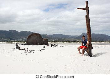 Man sitting at Shipwreck Kakapo at the beach of kommetjie