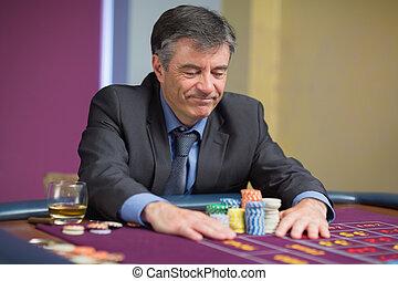 Man sitting at table looking at chips