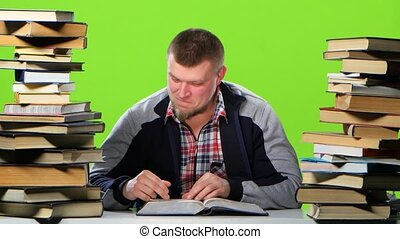 Man sitting at table with books and reading an interesting chapter. Green screen