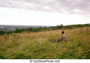 Man sitting at the field, watching at the valley, Iceland landscape