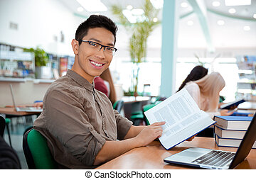 Man sitting at the table with book in university