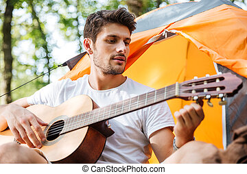 Man sitting at touristic tent and playing guitar in forest