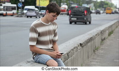 man sitting beside the road