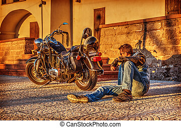 Man sitting by a classic motorcycle at dusk