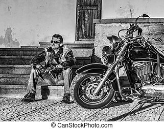 Man sitting by a classic motorcycle in black and white