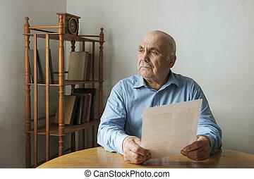 Man sitting contemplating a written document