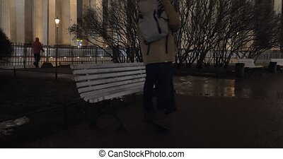 Man sitting down on the bench in park during evening walk