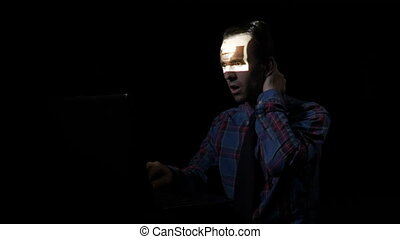 Man sitting in a dark room alone using computer and checking his social media account while the image screen is reflected on his face