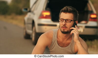 Man sitting in a front of broken with cell phone