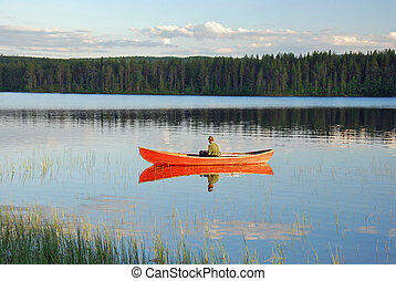 Man sitting in a red canoe on a lake in Finland and fishing...