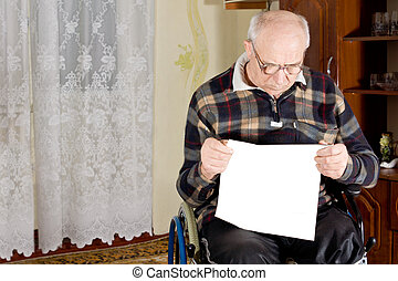 Man sitting in a wheelchair reading the newspaper