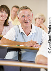 Man sitting in adult classroom laughing with students in background (selective focus)