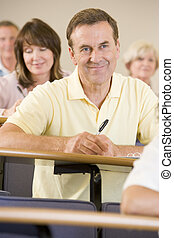 Man sitting in adult classroom with students in background (selective focus)
