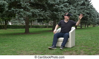 Man sitting in an armchair in the park looking at surroundings with virtual reality headset