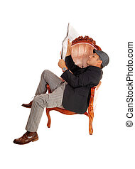 Man sitting in armchair reading paper.