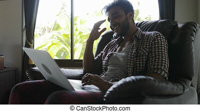 Man Sitting In Armchair Using Laptop Computer Typing Working...