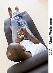 Man sitting in chair using personal digital assistant
