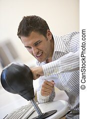 Man sitting in computer room using small punching bag for stress