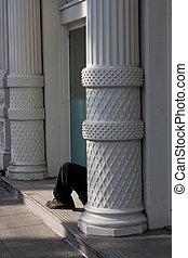 Man sitting in doorway on the street of Portland, Oregon.